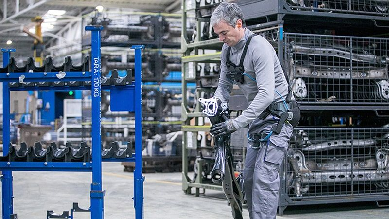 Factory employee with exoskeleton lifting steel