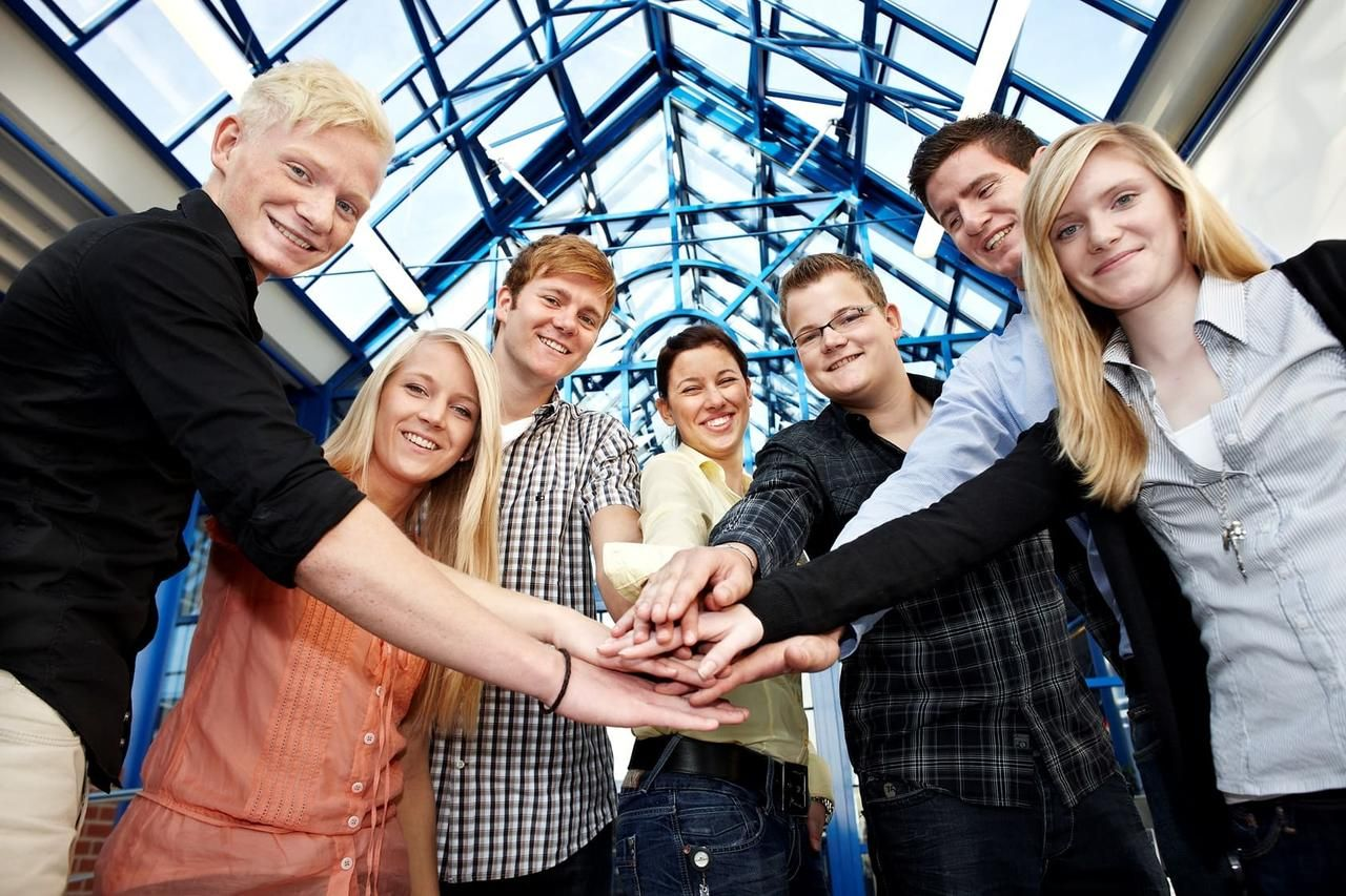 A group of youths holding their hands together